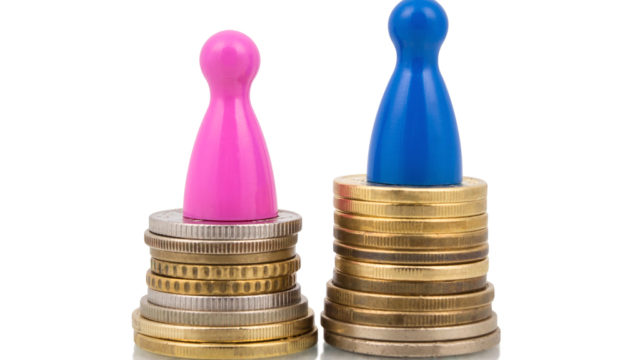 Pink and blue figures on different coin stacks. Concept for gender pay gap.